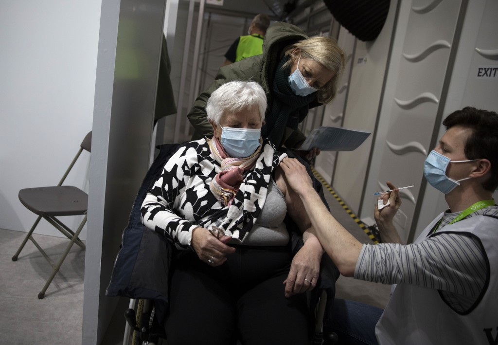 FILE - In this Tuesday, March 16, 2021 file photo, a woman receives a dose of the AstraZeneca COVID-19 vaccine at the Vaccine Village in Antwerp, Belg...