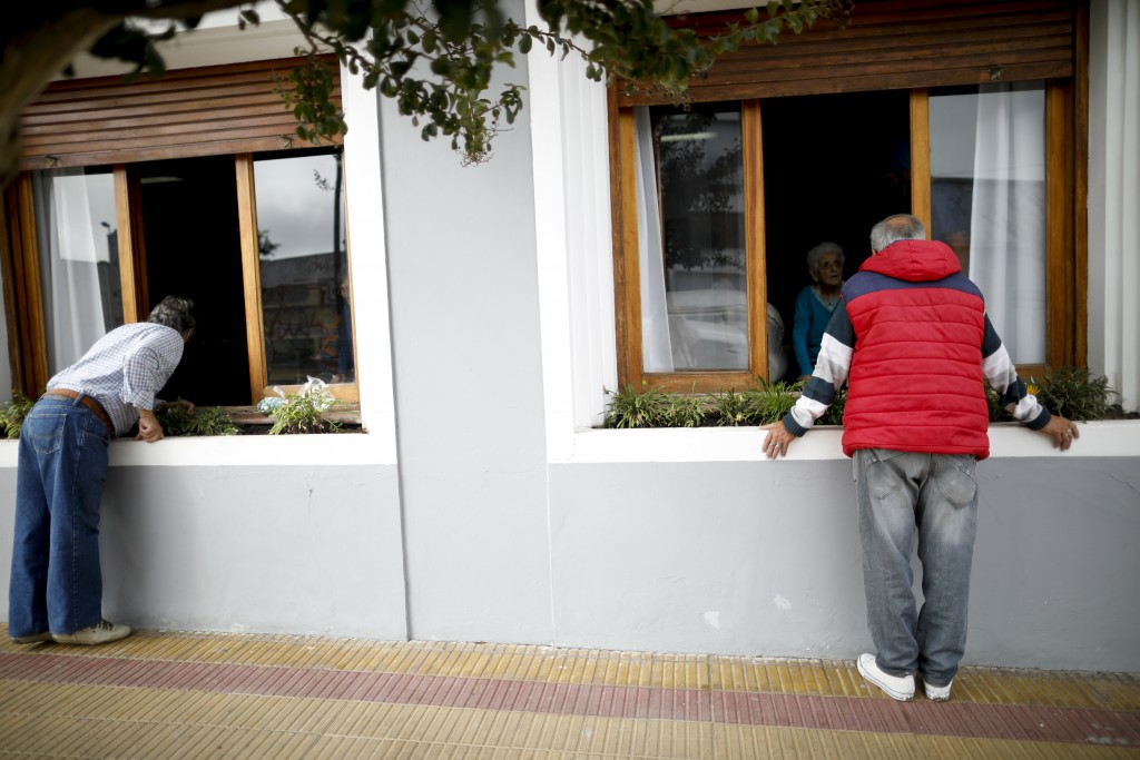 Men visit their mothers living at the Reminiscencias residence for the elderly in Tandil, Argentina, Monday, April 5, 2021. Residents here do not have...