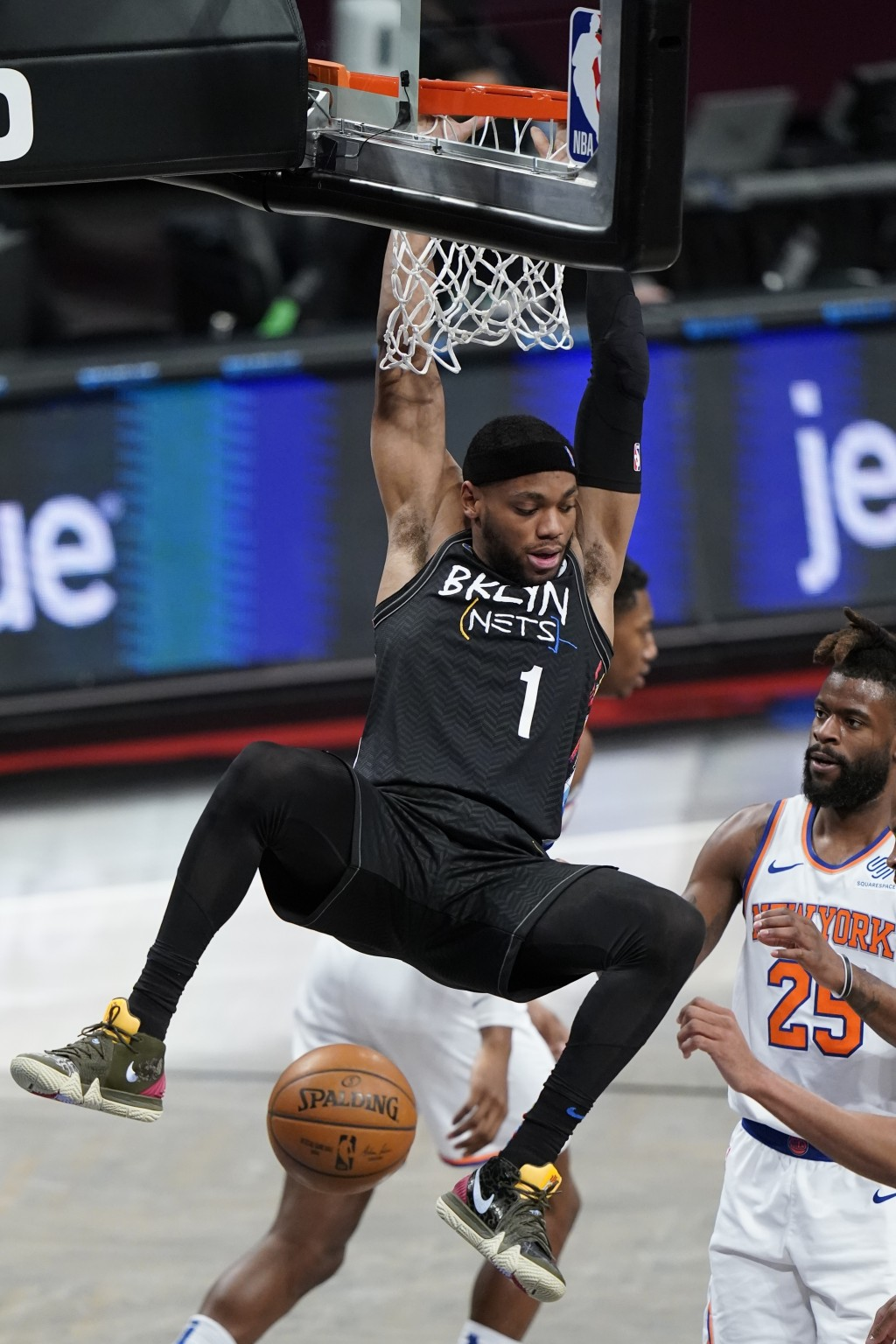 Brooklyn Nets' Bruce Brown (1) dunks the ball in front of New York Knicks' Reggie Bullock (25) during the first half of an NBA basketball game Monday,...