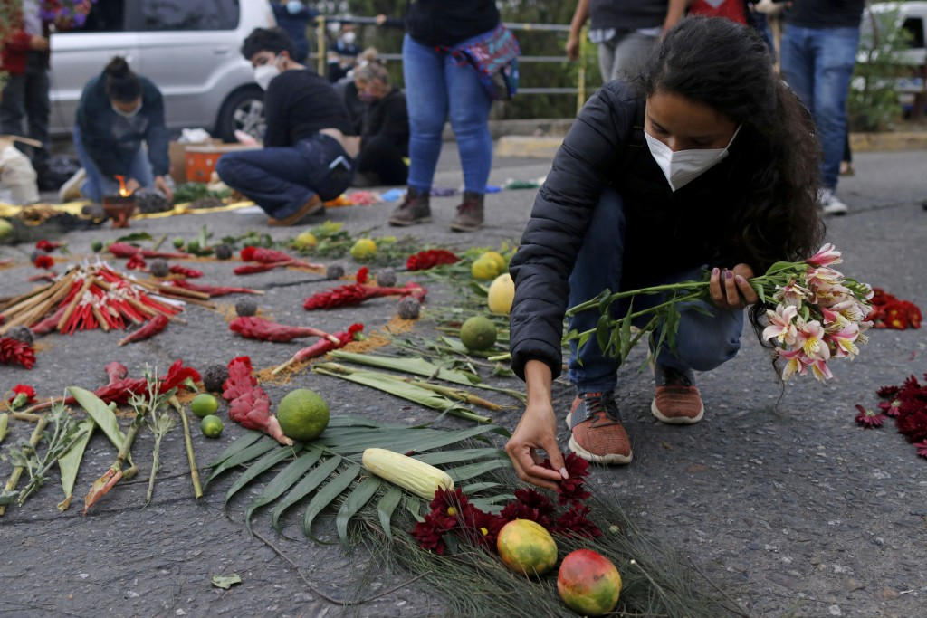 Berta Zuniga, a daughter of environmental and Indigenous rights activist Berta Caceres, places flower petal on an offering at a spiritual ceremony, a ...
