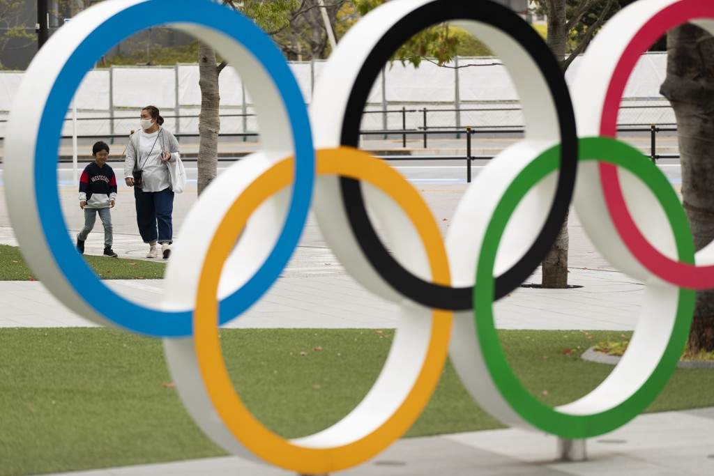 A mother and a boy walk by a display of the Olympic rings at the Japan Olympic Museum in Tokyo on Friday, April 2, 2021. Reports in Japan on Tuesday, ...