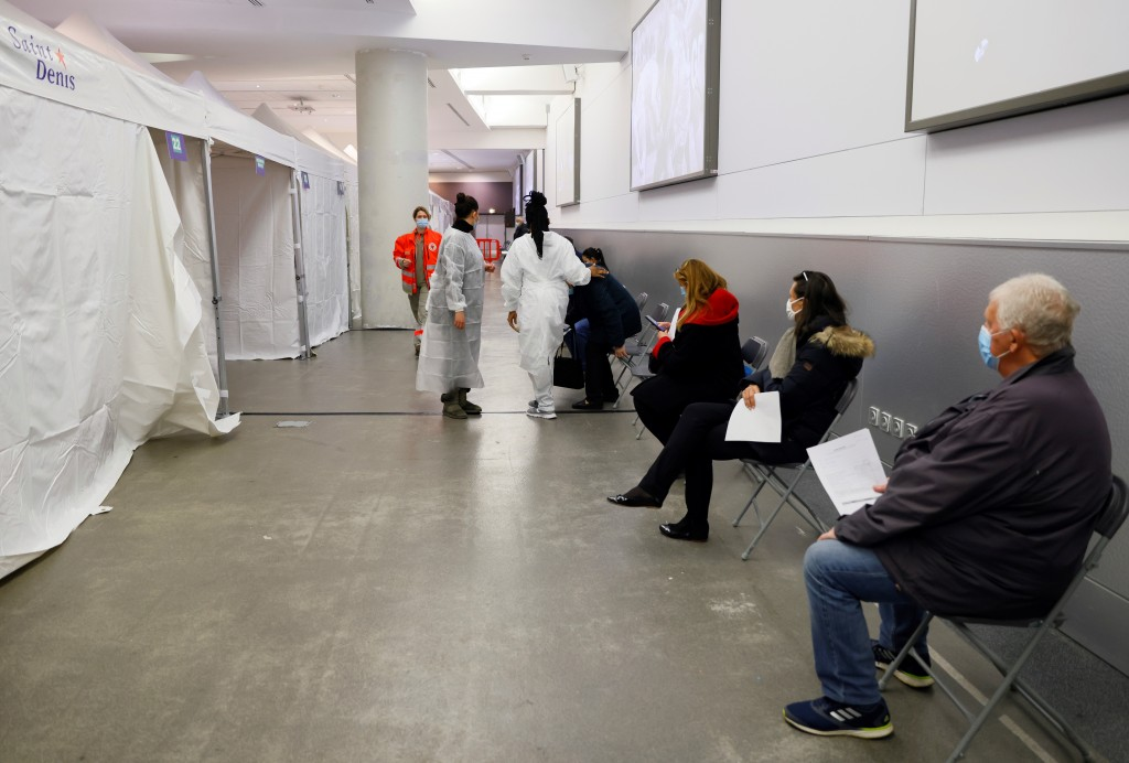 People wait to be vaccinated against Covid-19 at a vaccination centre set up at the Stade de France stadium in Saint-Denis, outside Paris, Tuesday, Ap...
