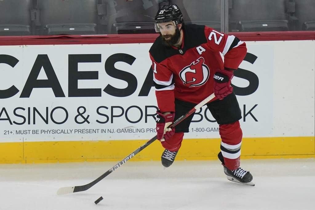 FILE - New Jersey Devils' Kyle Palmieri (21) moves the puck during the first period of an NHL hockey game against the Philadelphia Flyers in Newark, N...