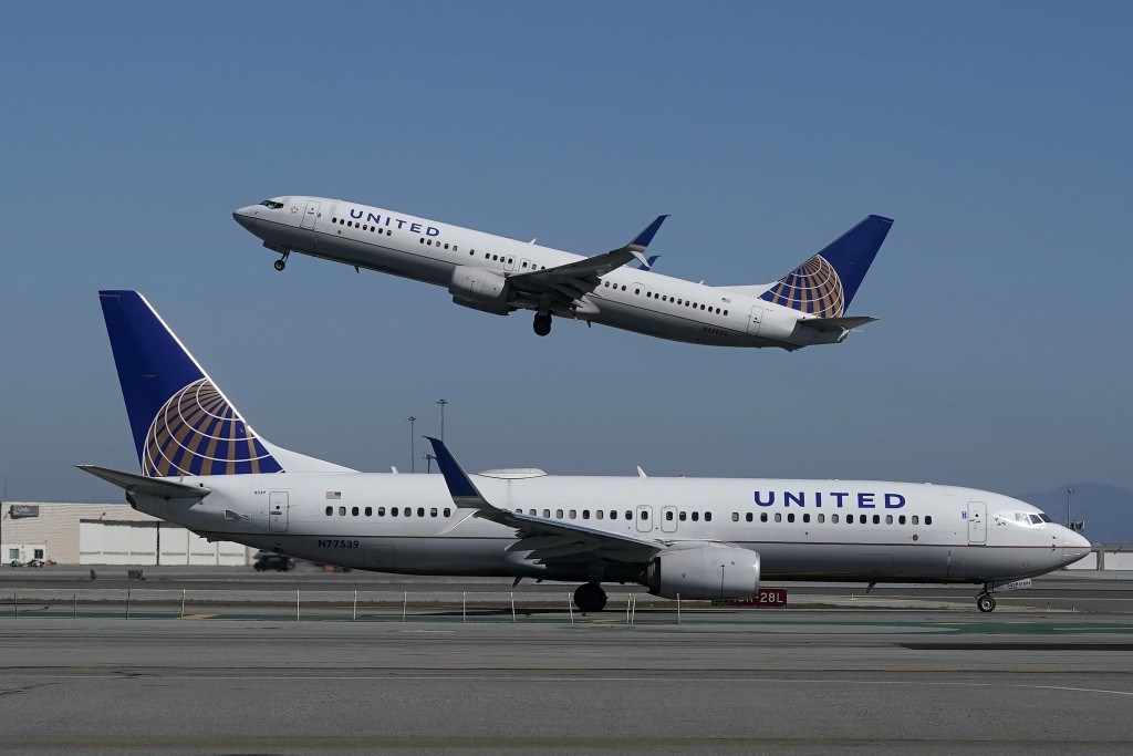 A United Airlines airplane takes off over a plane on the runway.