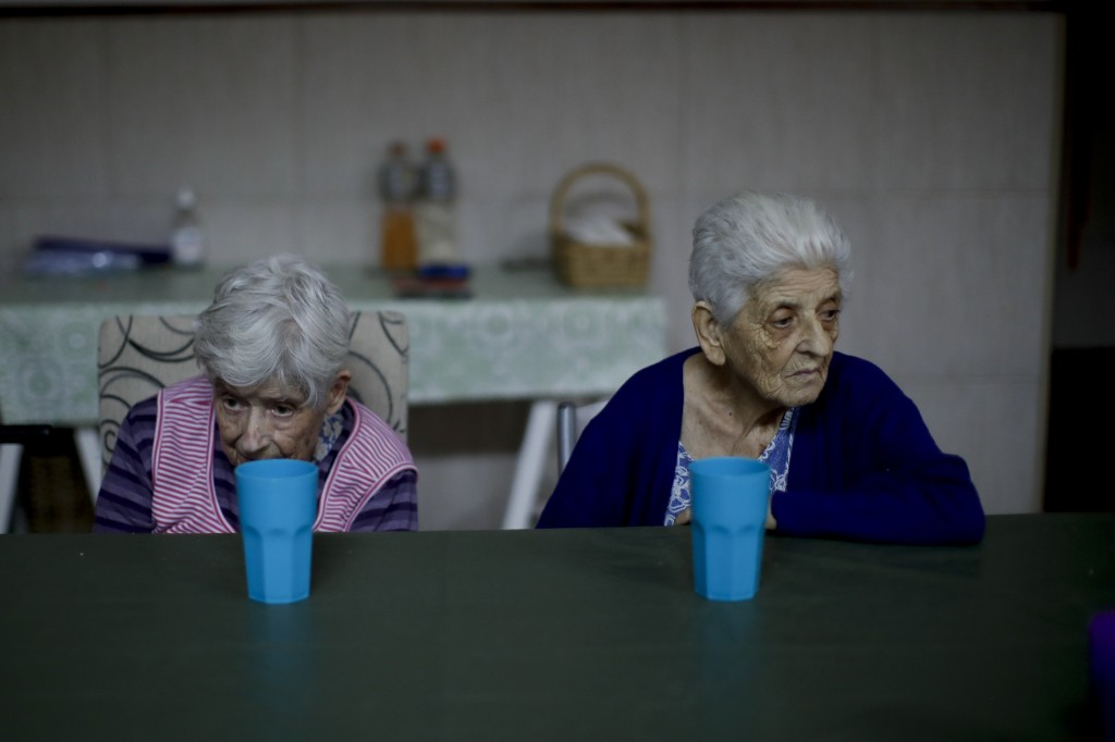 Elderly women rest at a table during a pause between activities at the Reminiscencias residence for the elderly in Tandil, Argentina, Sunday, April 4,...