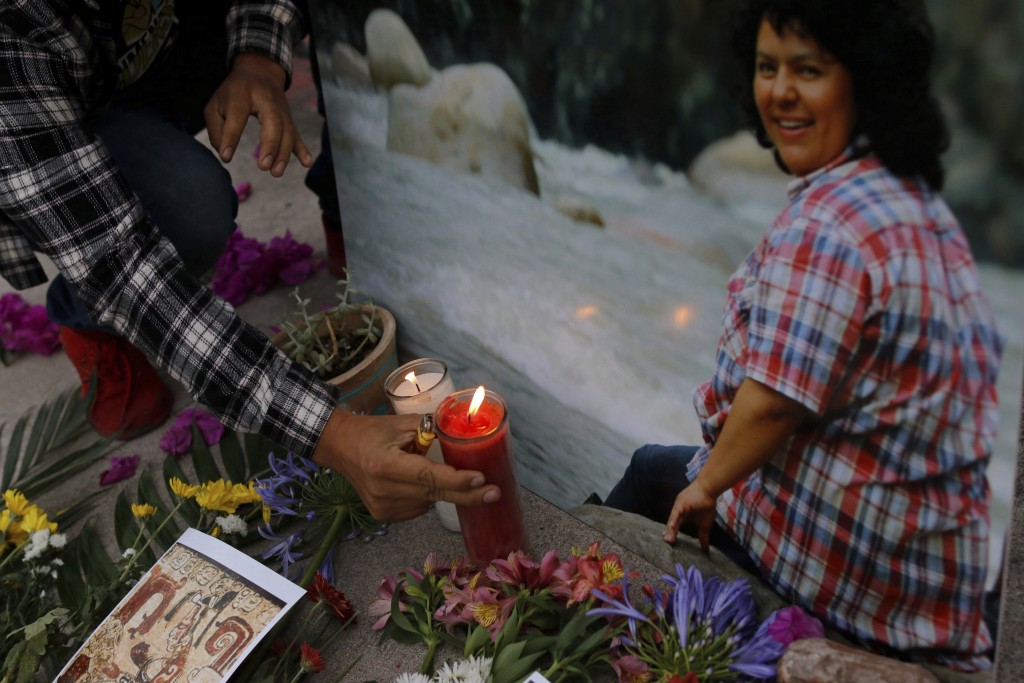 A man places a lit candle next to an image of environmental and Indigenous rights activist Berta Caceres at a spiritual ceremony, a day before a trial...