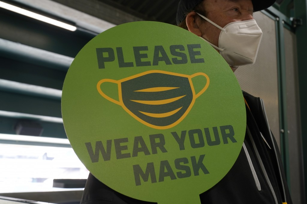 FILE - In this April 3, 2021, file photo, stadium worker holds up a sign for people to wear face masks before a baseball game between the Oakland Athl...
