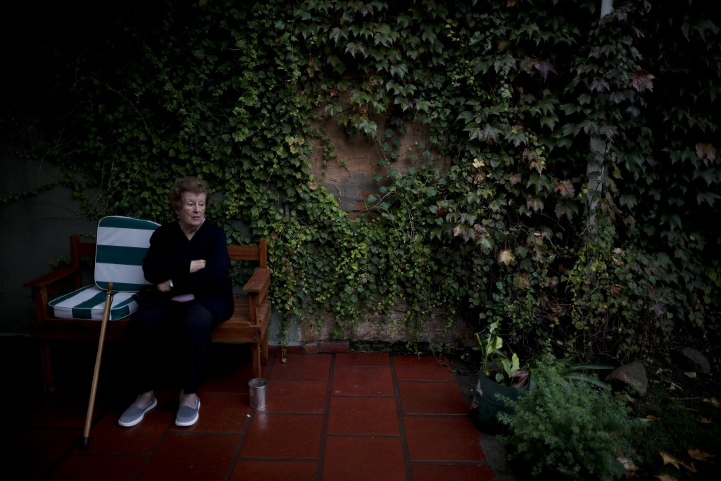 Thelma Amezua sits in the garden at the Reminiscencias residence for the elderly in Tandil, Argentina, Monday, April 5, 2021. Residents here do not ha...