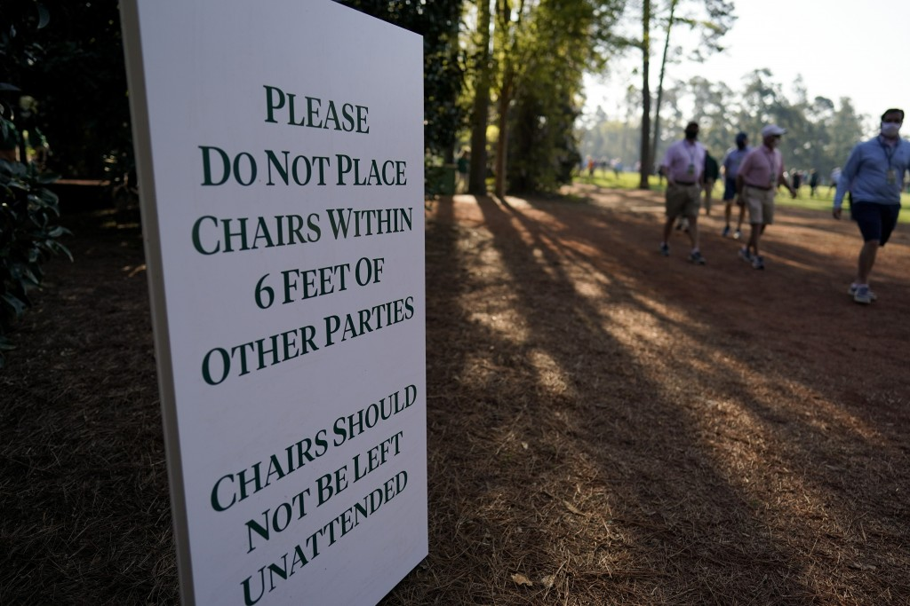 A sign posted on the course urges patrons to social distance during a practice round for the Masters golf tournament on Tuesday, April 6, 2021, in Aug...