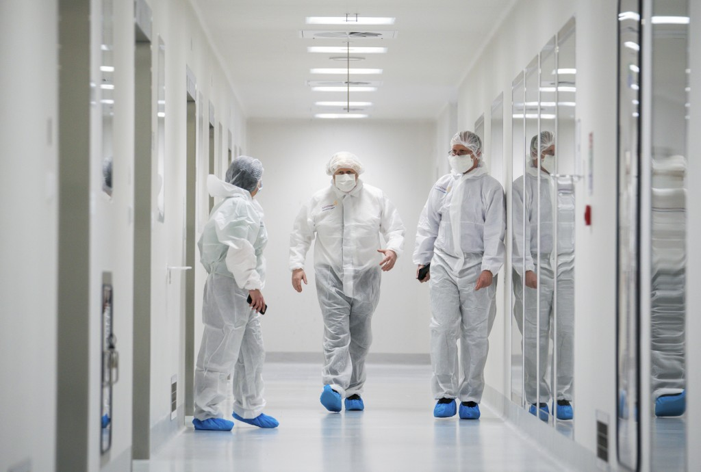 Britain's Prime Minister Boris Johnson, centre, dressed in protective gear is guided during a visit to the AstraZeneca facility in Macclesfield, Engla...