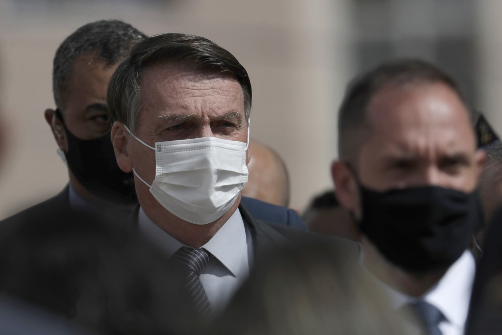 Wearing a mask to curb the spread of the new coronavirus, Brazil's President Jair Bolsonaro arrives for a ceremony to deliver affordable homes built b...
