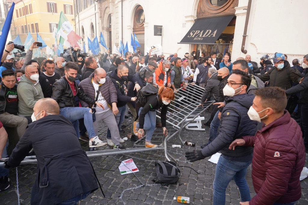 Demonstrators step on barriers set up by Italian Police during a protest by Restaurant owners and workers outside the Lower Chamber in Rome, Tuesday, ...