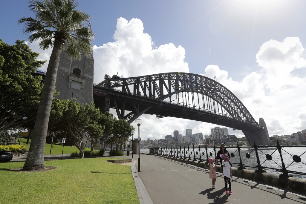 A woman and 2 children walk under the Harbour Bridge in a popular area in Sydney, Australia, Tuesday, April 6, 2021. New Zealand announced the start d...