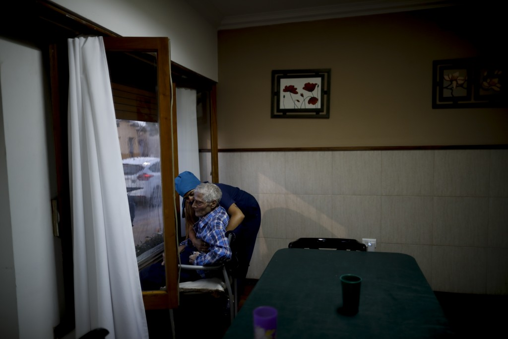 Nurse Rocio Lescano, 86, helps Victor Tripiana in his chair in front of a window where he visits with his family on the other side, at the Reminiscenc...