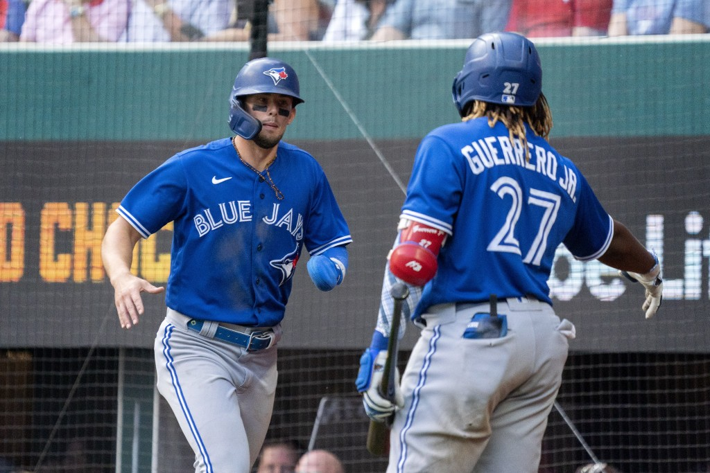 Toronto Blue Jays' Cavan Biggio, left, is congratulated by Vladimir Guerrero Jr. (27) after scoring on a ground ball by Teoscar Hernandez during the s...