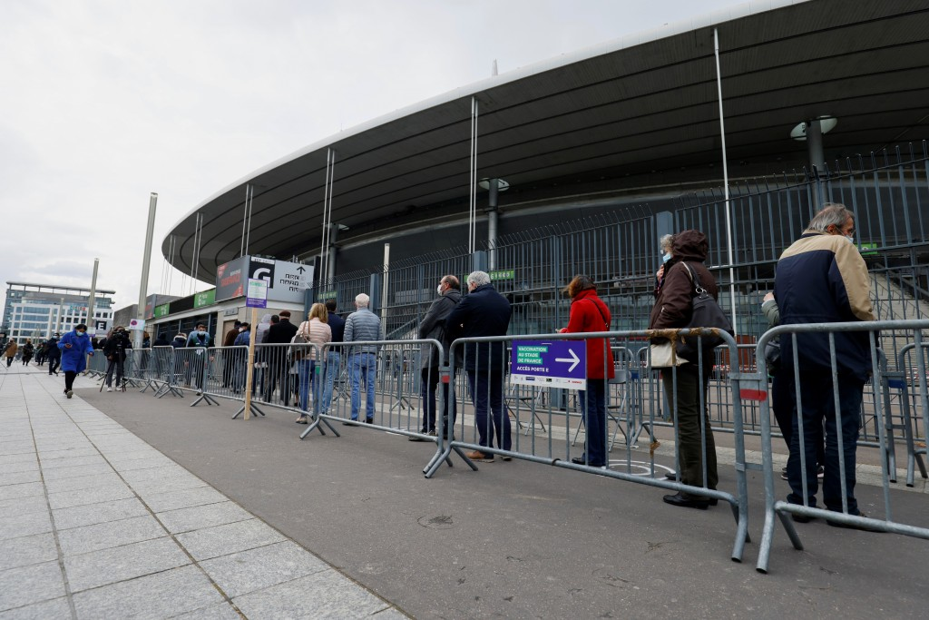 People queue as they arrive at the Stade de France stadium to be vaccinated against COVID-19 in Saint-Denis, outside Paris, Tuesday, April 6, 2021. Wh...