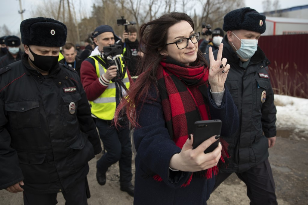 Activist Ksenia Pakhomova, foreground, takes a selfie as police officers detain her at the prison colony IK-2, which stands out among Russian penitent...
