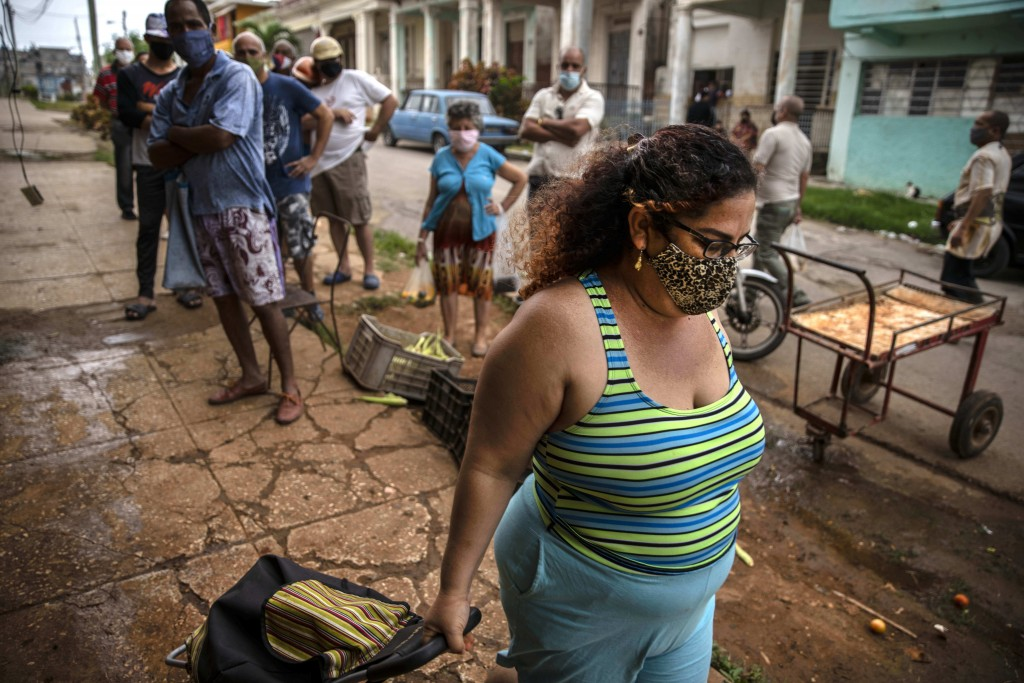 Yuliet Colon pulls her rolling grocery cart as she walks home after after a visit to the agro market in Havana, Cuba, Friday, April 2, 2021. Colon hel...