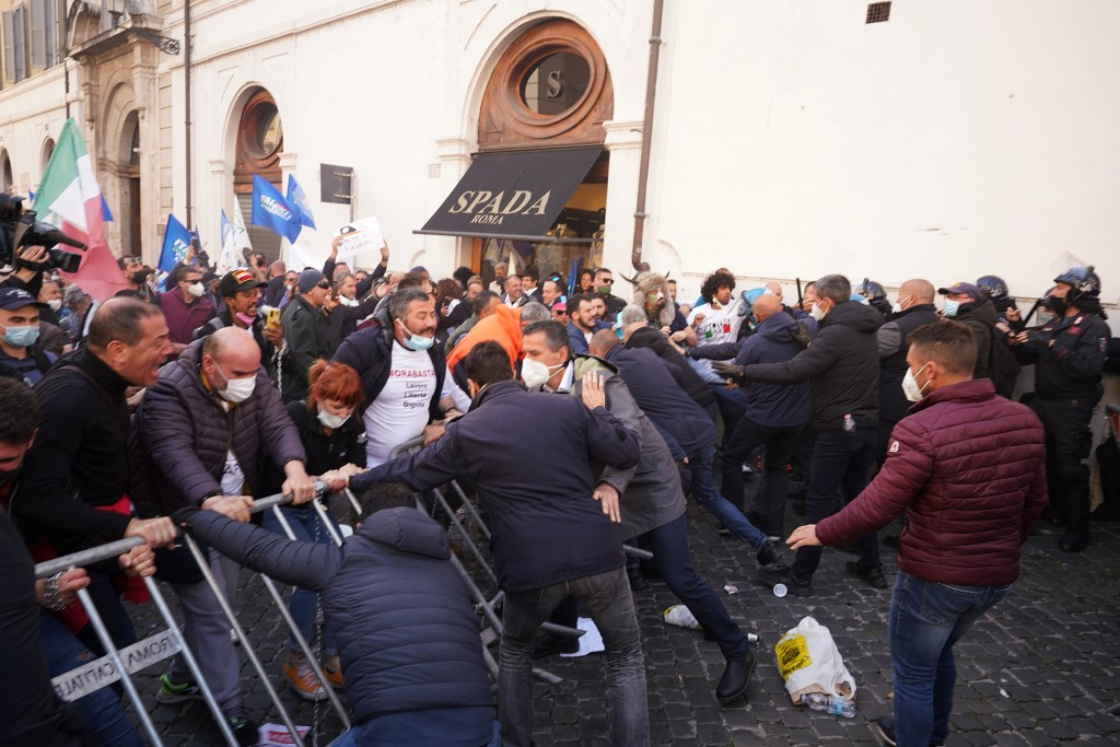 Demonstrators scuffle with Italian Policemen during a protest by Restaurant and shop owners outside the Lower Chamber in Rome, Tuesday, April 6, 2021....