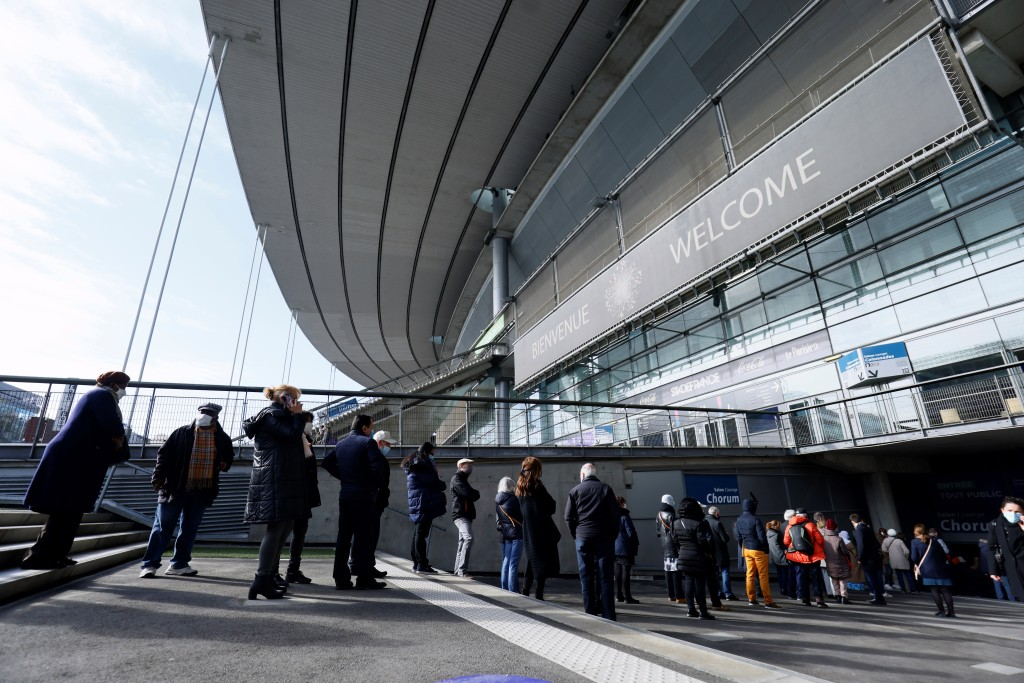 People arrive at the Stade de France stadium to be vaccinated against Covid-19 in Saint-Denis, outside Paris, Tuesday, April 6, 2021. While France rem...