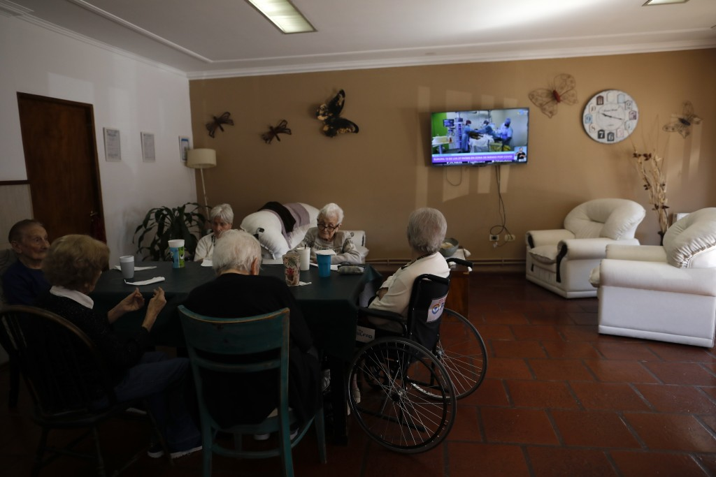 Women sit together at the Reminiscencias residence for the elderly in Tandil, Argentina, Monday, April 5, 2021. Residents here do not have physical co...