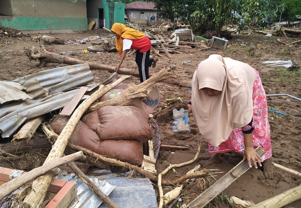 Women clear flood debris in the village in Waiwerang, on Adonara Island, easter Indonesia, Tuesday, April 6, 2021. Rescuers in remote eastern Indonesi...