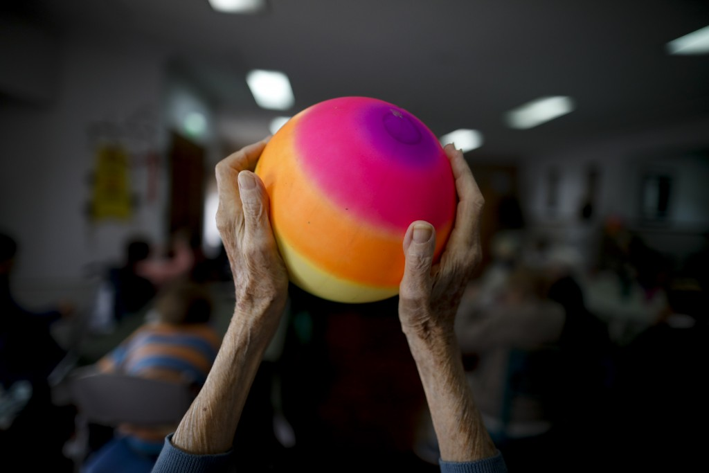 Delia Solbach holds up a ball during an exercise class at the Reminiscencias residence for the elderly in Tandil, Argentina, Monday, April 5, 2021. Re...