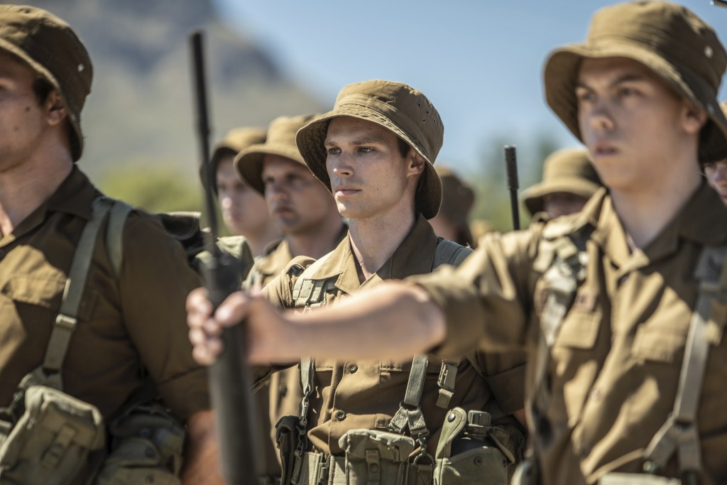 """This image released by IFC Films shows Kai Luke Brummer, center, in a scene from """"Moffie."""" (IFC Films via AP)"""