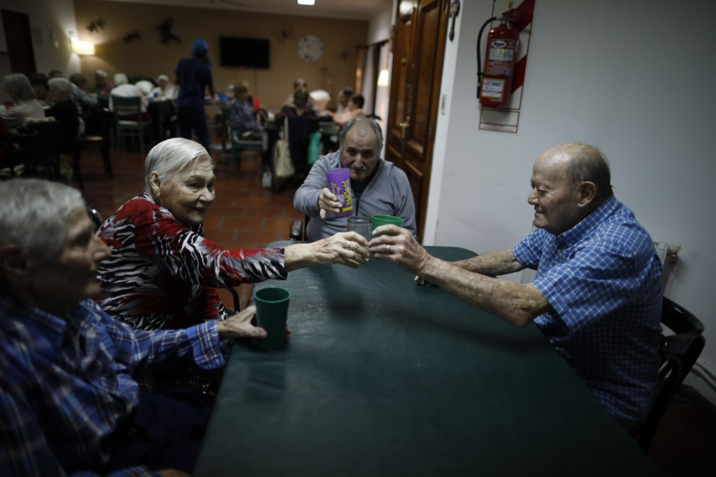 Seniors, from left, Victor Tripiana, Catalina Pisicelli, Pedro Aberastegui and Fermin Urban make a toast before dinner at Reminiscencias residence in ...