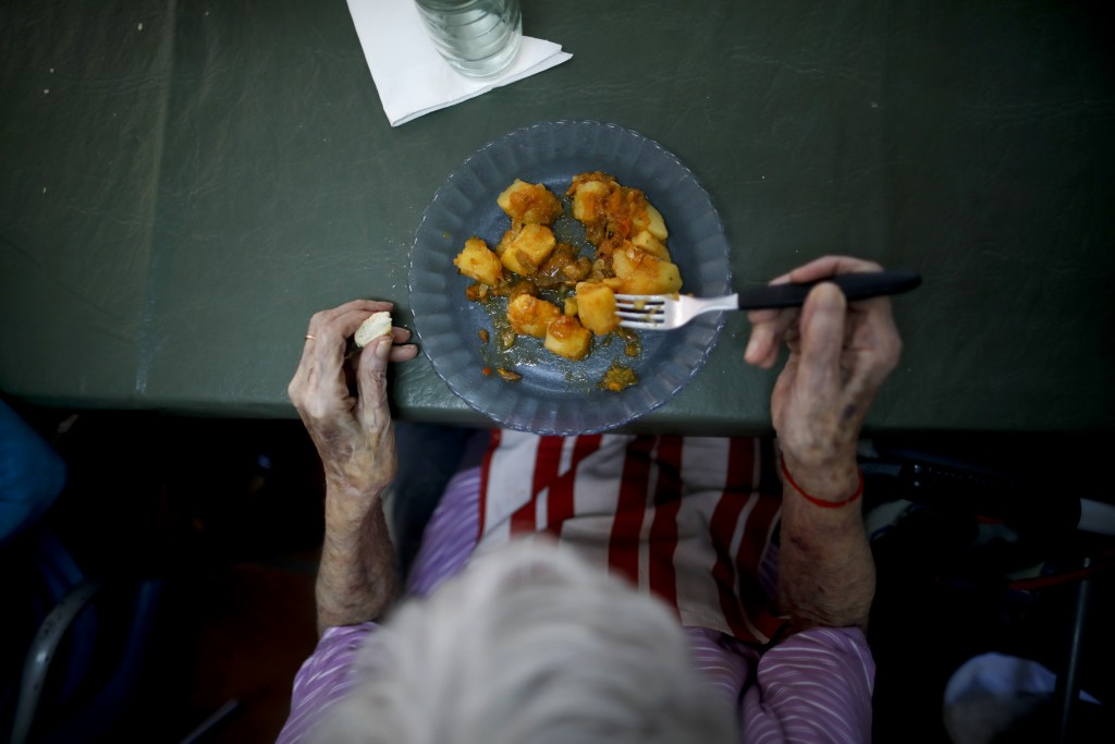 A woman eats lunch at the Reminiscencias residence for the elderly in Tandil, Argentina, Monday, April 5, 2021. Residents here do not have physical co...