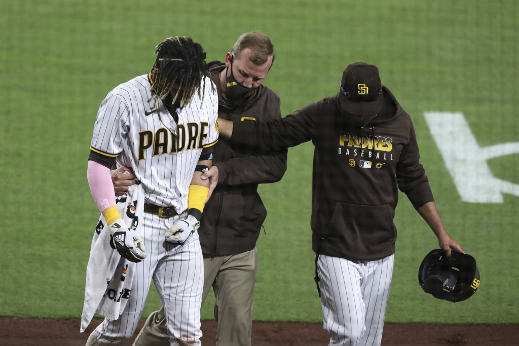 San Diego Padres manager Jayce Tingler, right, and a trainer help Fernando Tatis Jr, left, off the field after Tatis hurt his shoulder while swinging ...