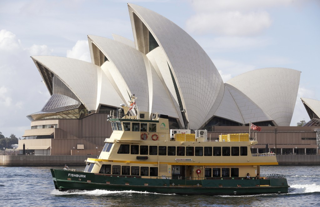 A ferry sails past the Opera House in Sydney, Australia, Tuesday, April 6, 2021. New Zealand announced the start date for a long-anticipated travel bu...