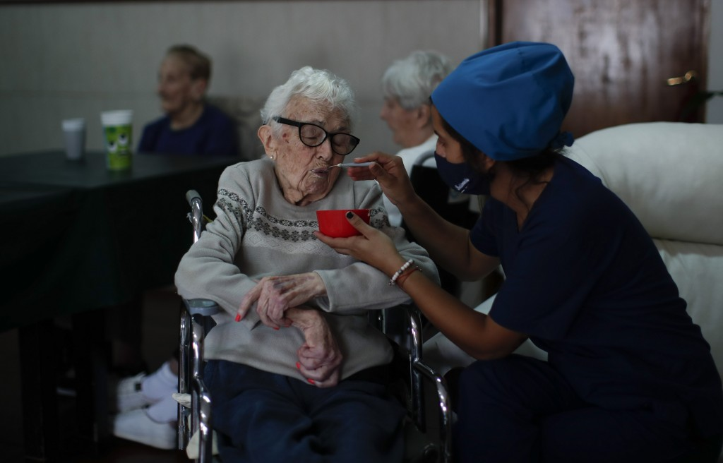 Nurse Rocio Lescano feeds Dora Amestoy her breakfast at the Reminiscencias residence for the elderly in Tandil, Argentina, Monday, April 5, 2021. Resi...