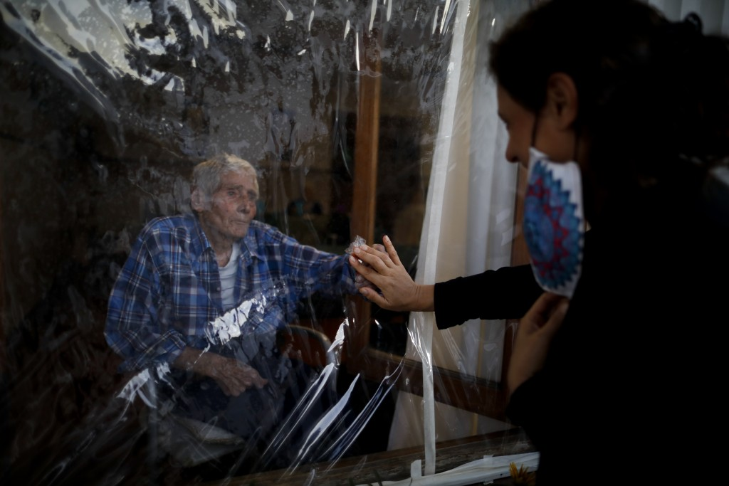 Victor Tripiana, 86, reaches out to touch the hand of his daughter-in-law Silvia Fernandez Sotto, separated by a plastic sheet to prevent the spread o...