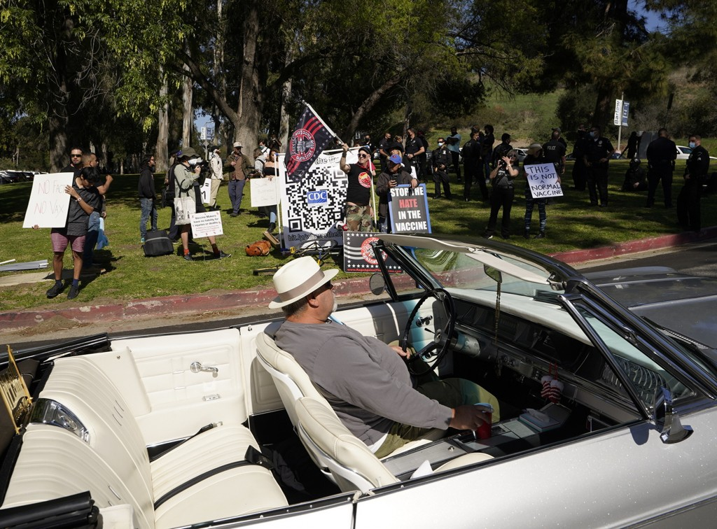 FILE - In this Feb. 27, 2021, file photo, a driver in his convertible cruises past a small group of anti-COVID-19 vaccine protesters demonstrating at ...