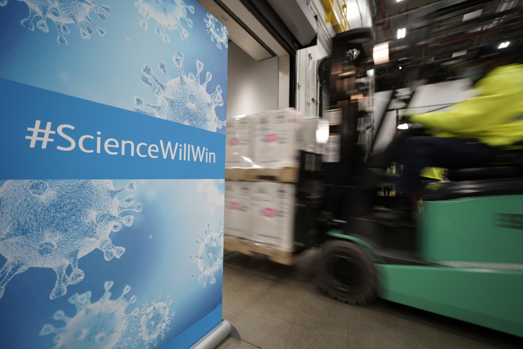 FILE - In this Dec. 13, 2020, file photo, boxes containing the Pfizer-BioNTech COVID-19 vaccine are loaded onto a truck for shipping at the Pfizer Glo...