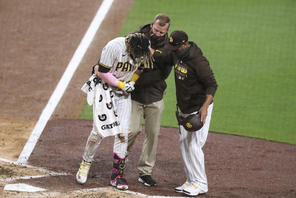 San Diego Padres manger Jayce Tingler, right, and a trainer, center, help Fernando Tatis Jr., left, off the field after Tatis hurt his shoulder while ...