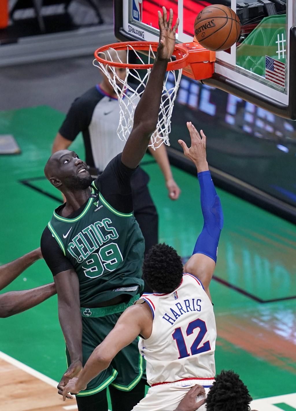 Boston Celtics center Tacko Fall (99) reaches to block a shot by Philadelphia 76ers forward Tobias Harris (12) during the first half of an NBA basketb...