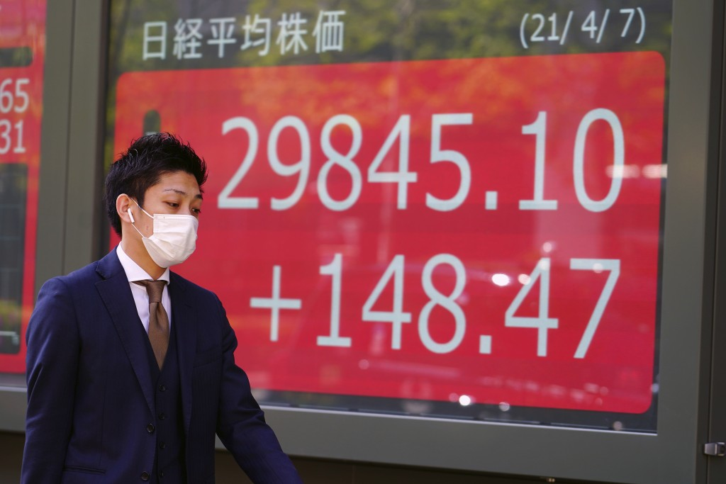 A man wearing a protective mask walks in front of an electronic stock board showing Japan's Nikkei 225 index at a securities firm Wednesday, April 7, ...