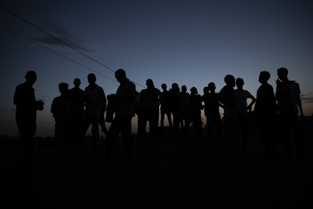 Tigrayan refugees who fled the conflict in the Ethiopia's Tigray gather after the sun sets in Hamdayet, eastern Sudan, near the border with Ethiopia, ...