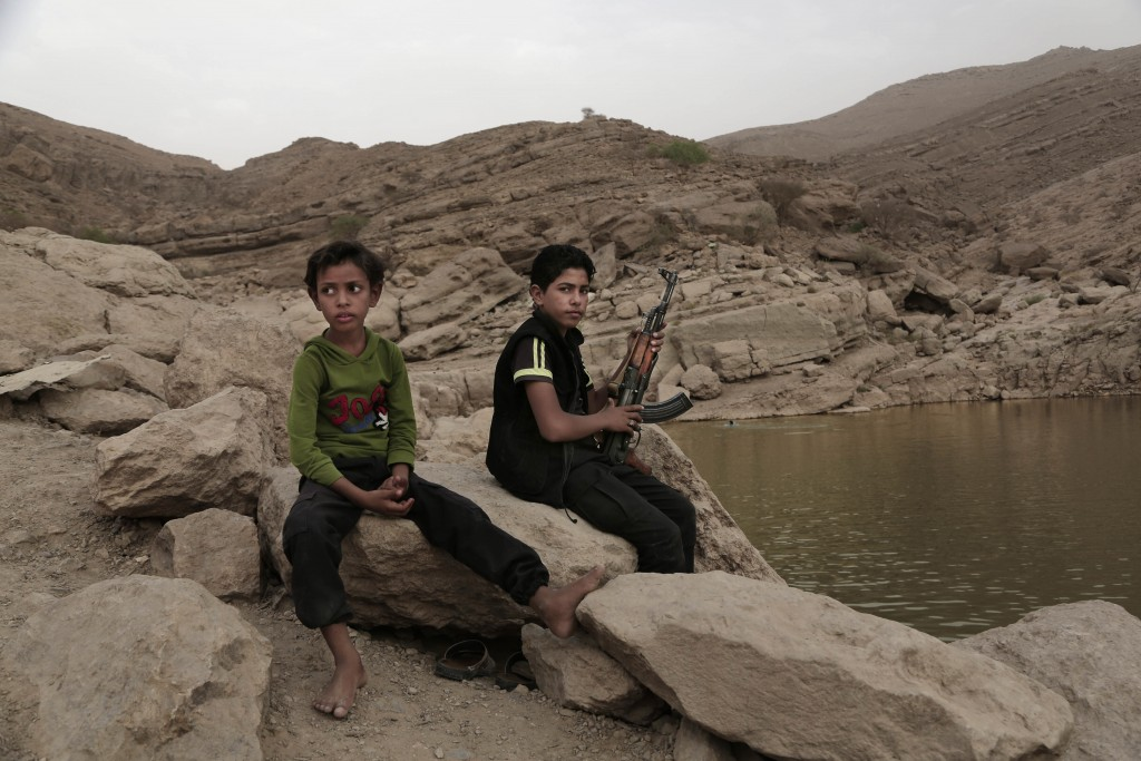 FILE - In this July 30, 2018, file photo, a 17-year-old boy holds his weapon at the dam in Marib, Yemen. The battle for the ancient desert city has be...