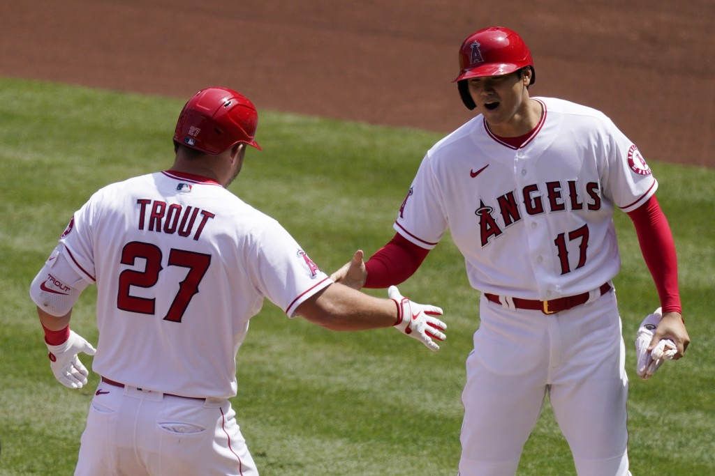 Los Angeles Angels' Mike Trout, left, is congratulated by Shohei Ohtani after hitting a two-run home run during the first inning of a baseball game ag...