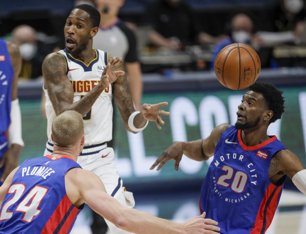 Denver Nuggets forward Will Barton, left, passes between Detroit Pistons center Mason Plumlee (24) and guard Josh Jackson (20) in the first quarter of...