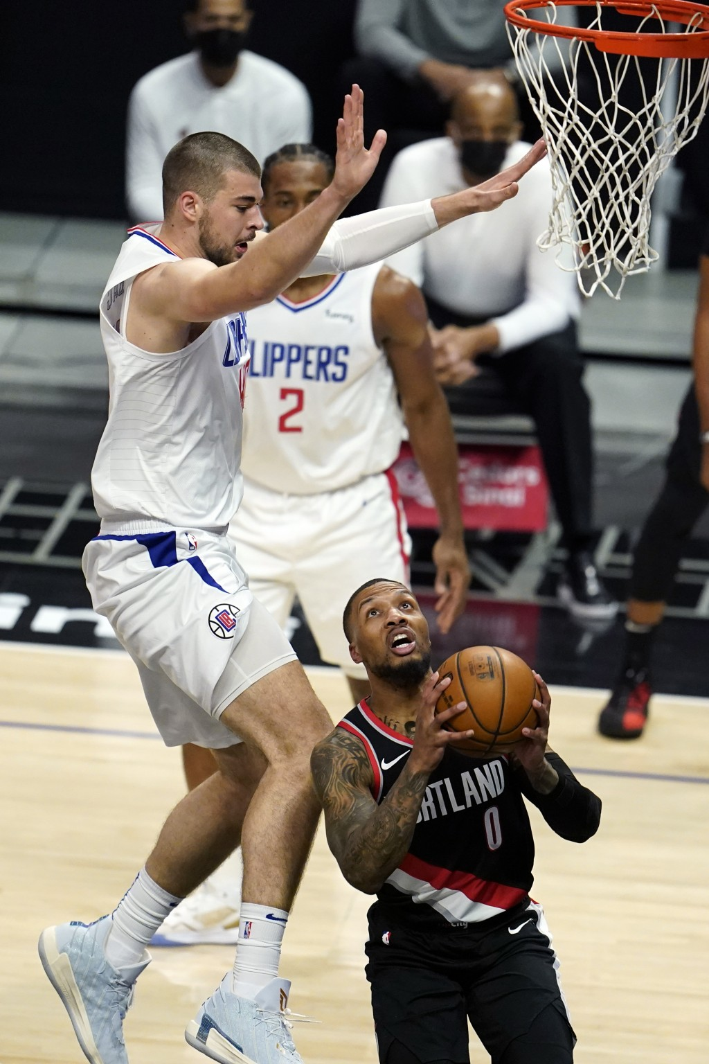 Portland Trail Blazers guard Damian Lillard (0) drives to basket as Los Angeles Clippers center Ivica Zubac, left, defends during the first half of an...