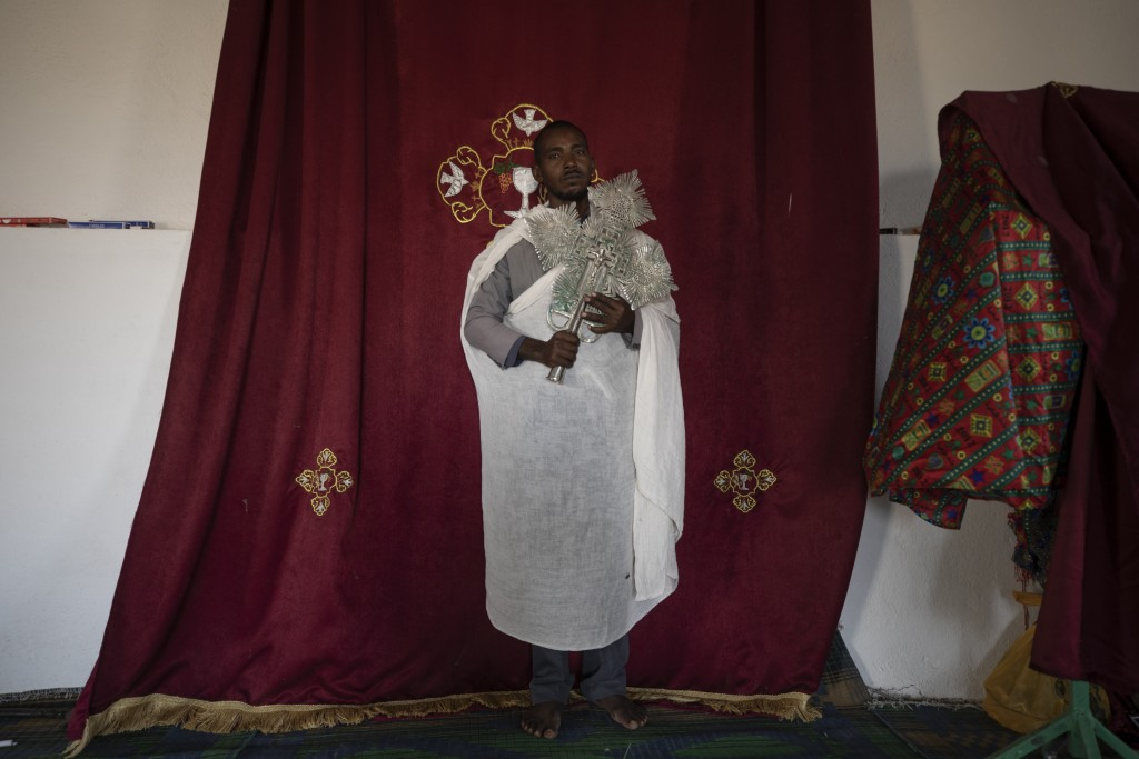 Ordained priest Berhane Debesu, 34, a Tigrayan refugee from Humera, stands with a cross at the church in Hamdayet, eastern Sudan, near the border with...