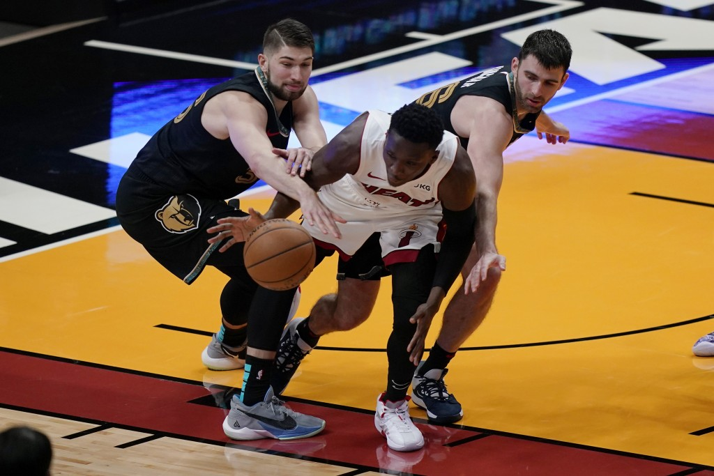 Miami Heat guard Victor Oladipo, middle, and Memphis Grizzlies center Killian Tillie, left, and guard John Konchar (46) go after the ball during the s...
