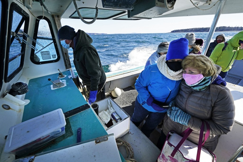 Nurses Kathy Cheney, wearing hat, and Maureen Giffen huddle on a wet and windy ride aboard a lobster boat on the way to set up a COVID-19 vaccination ...