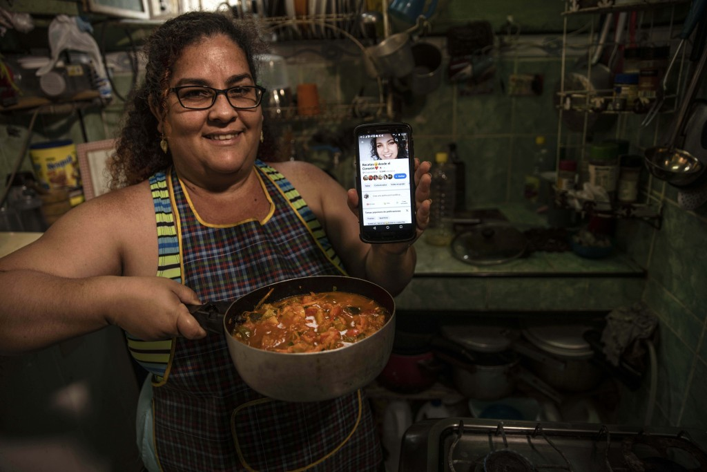 """Contributor Yuliet Colon poses for a photo holding a pot of her creation, """"Cuban-style pisto manchego,""""  and her phone that displays the Facebook page..."""