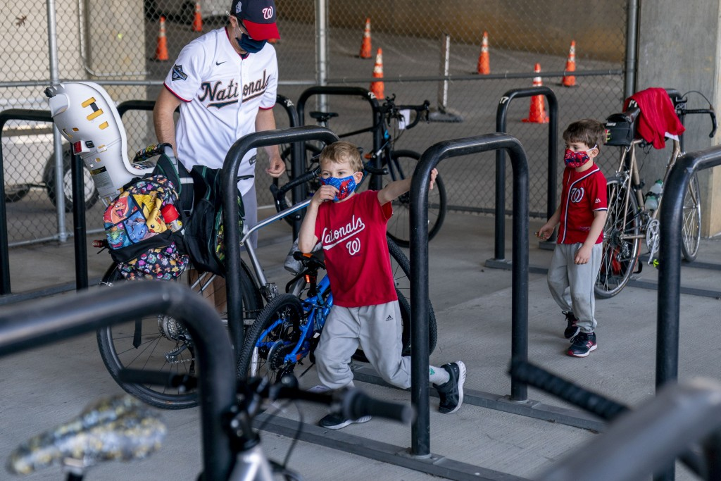 Michael Hoffman of Washington and his sons Evan, 6, center, and Andrew, 4, right, lock up their bikes as they arrive before the Washington Nationals p...