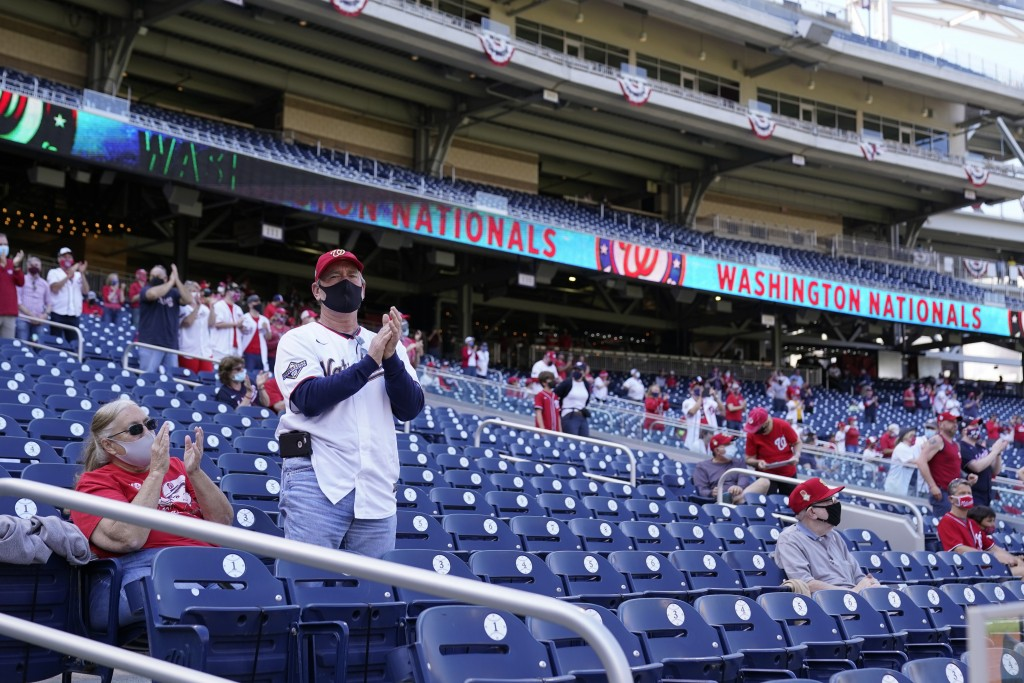 Fans sit socially-distanced in the stands before an opening day baseball game between the Atlanta Braves and the Washington Nationals at Nationals Par...